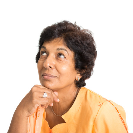ethnic woman: Portrait of a 50s Indian mature woman smiling and looking up having a thought, isolated on white background.