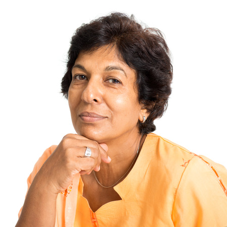 Portrait of a happy 50s Indian mature woman smiling and looking at camera, isolated on white background.