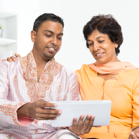 home grown: Portrait of Indian family using social media at home. Mature 50s Indian woman and son looking at tablet computer.