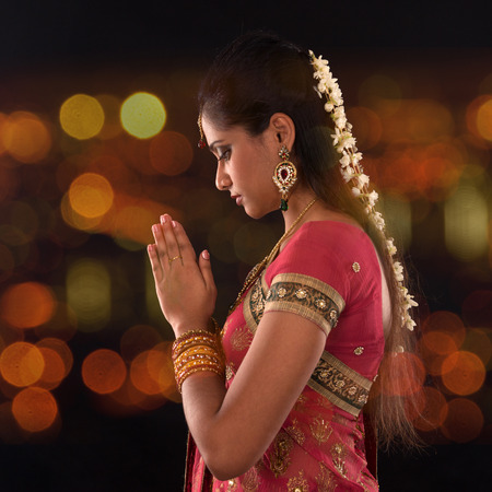 indian saree: Indian woman in traditional sari praying and celebrating Diwali or deepavali, fesitval of lights at temple. Female prayer hands folded, beautiful lights bokeh background.