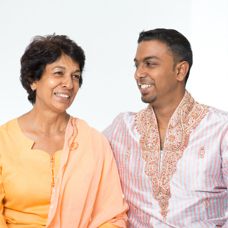 elderly woman: Portrait of happy Indian family communicating at home. Mature 50s Indian mother and her 30s grown son.
