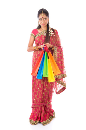 happy customer: Indian girl in traditional sari shopping for diwali festival, full length standing isolated on white background.