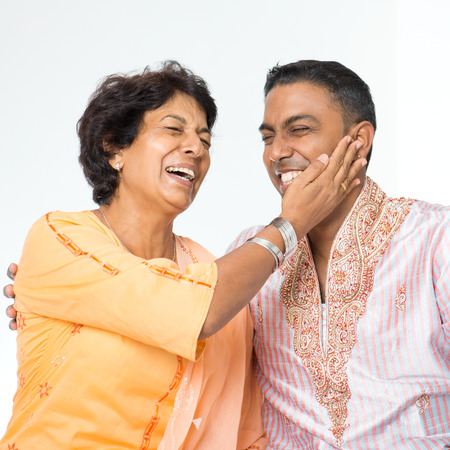 50s: Portrait of happy Indian family having fun conversation at home. Mature 50s Indian mother and her 30s grown son. Stock Photo