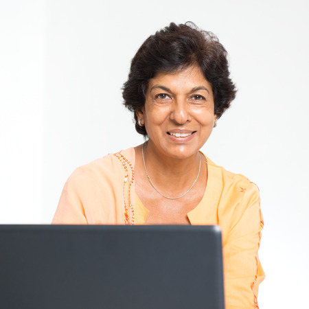 Elder people and modern technology concept. Portrait of a 50s Indian mature woman using internet at home. Indoor senior people living lifestyle. Banque d'images