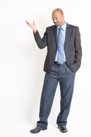 hand pointing: Portrait of full body mature Indian business man hand showing something, standing on plain background.