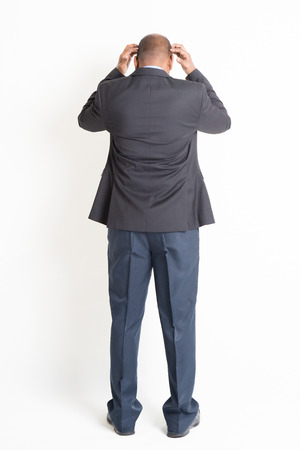 hands on head: Rear view full body mature Indian business man hands scratching head and running out of idea , standing on plain background.