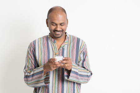 Portrait of mature casual business Indian man using smartphone, mobile apps concept, standing on plain background with shadow.