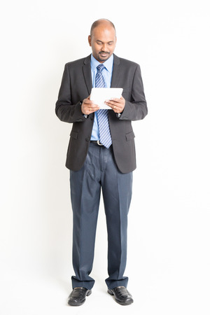 white person: Full body Asian Indian businessman using digital tablet computer standing over plain background