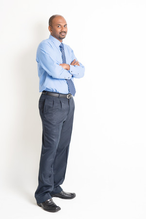 asian business man: Portrait of full body mature Indian business man with blue shirt arms crossed standing on plain background.