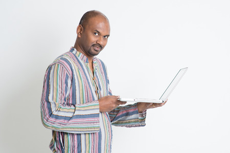 using computer: Side view of mature casual business Indian man using laptop computer, looking at camera, standing on plain background with shadow.