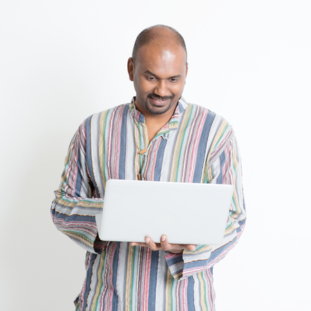 computer isolated: Portrait of mature casual business Indian male using laptop computer, standing on plain background with shadow.
