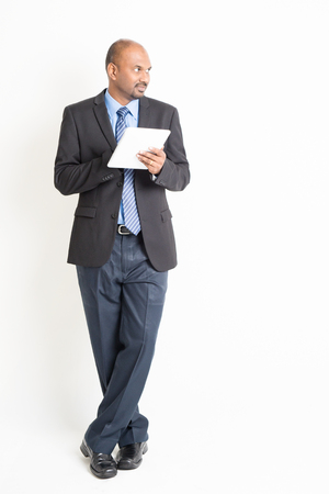 tab: Full body Asian Indian businessman using digital tablet computer, looking at side copy space, standing over plain background