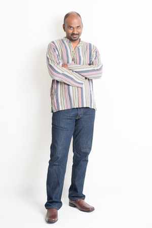 male body: Full body confident mature Indian man in casual wear standing on plain background with shadow. Stock Photo