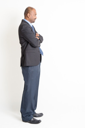 Side view full body mature Indian business man arms crossed, standing on plain background.