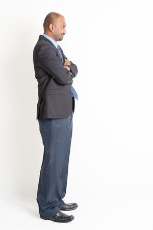 cuerpo humano: Vista lateral de cuerpo completo maduro hombre de negocios indio con los brazos cruzados, de pie en el fondo plano.