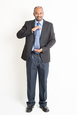 open hands: Full body mature Indian business man with cupped hands as if holding something, standing on plain background.