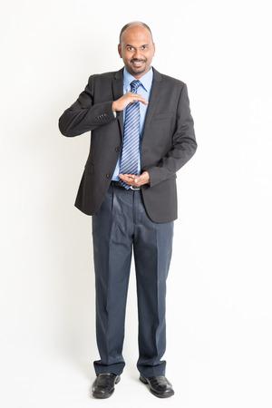 manos abiertas: Todo el cuerpo del hombre de negocios indio maduro con las manos ahuecadas, como si estuviera sosteniendo algo, de pie en el fondo plano.