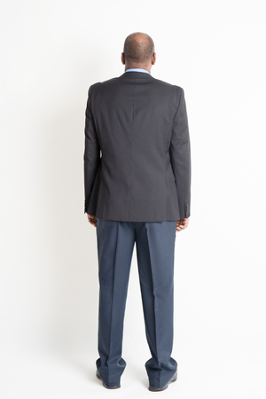 Rear view full body mature Indian business man standing on plain background.