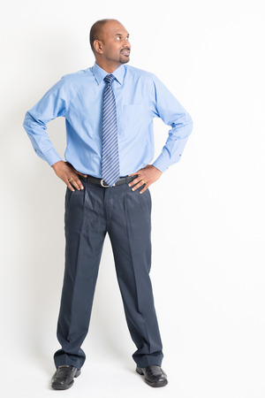 the whole body: Portrait of full body mature Indian business man hands on waist looking to side, standing on plain background. Stock Photo