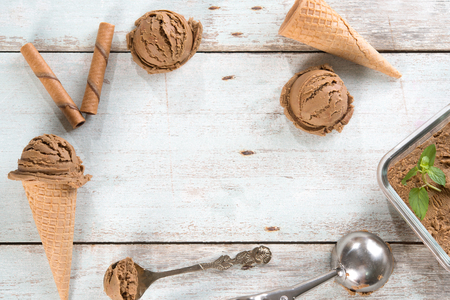 Top view brown ice cream in waffle cone with utensil on rustic wooden background. Copy space on middle.