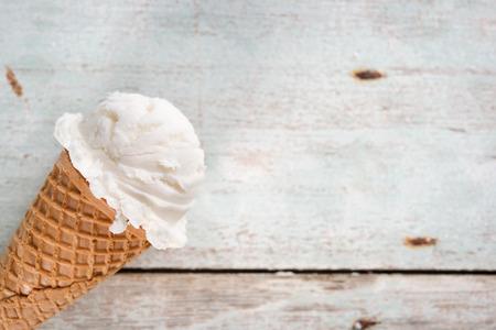 ice cream design: Single vanilla ice cream in a waffle cones over wooden background.