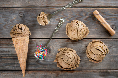scoop: Top view brown ice cream in waffle cone on old rustic vintage wooden background.