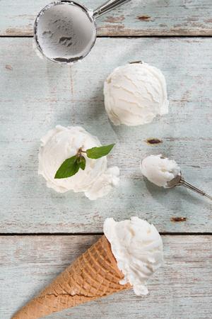 Top helados vista vainilla en cono de la galleta con el utensilio en el fondo de madera. Foto de archivo - 45969247