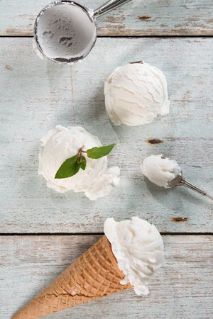 coconut: Top view vanilla ice cream in waffle cone with utensil on wood background.