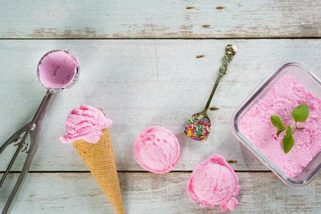 Vista dall'alto di gelato rosa nel cono di cialda con utensile su fondo rustico in legno. Archivio Fotografico - 45969266