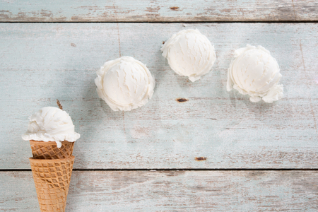 Bovenaanzicht bolletje vanille-ijs in wafel kegel op hout achtergrond.