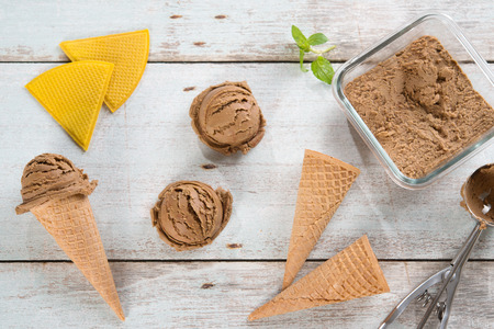 scoop: Top view brown ice cream in waffle cone with utensil on rustic wooden background.