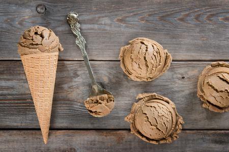 Top gelato vista di cioccolato in cialda cono sul vecchio fondo rustico di legno d'epoca. Archivio Fotografico - 45969318