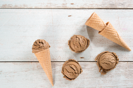 Top view cocoa ice cream in waffle cone on rustic wooden background. Stock Photo