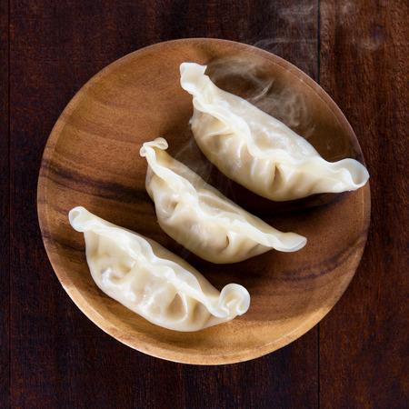 Bovenaanzicht close up verse dumplings met hete stoom op houten plaat. Chinees voedsel op rustieke oude vintage houten achtergrond. Stockfoto