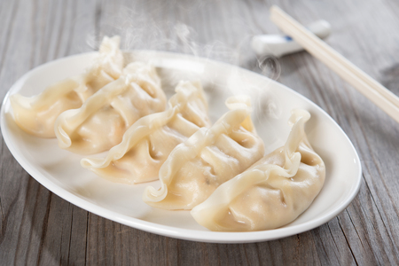 Fresh boiled dumpling on plate. Chinese food with hot steams on old wooden background.