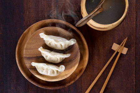 dim: Top view fresh dumplings with hot steams on wood plate with chopsticks. Chinese food on rustic old vintage wooden background.