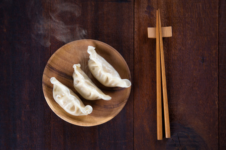 chinese meal: Top view fresh dumplings with hot steams on wood plate with chopsticks. Chinese meal on rustic old vintage wooden background.