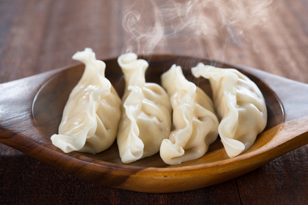 Close up fresh dumplings with hot steams on wood plate. Chinese gourmet on rustic old vintage wooden background.