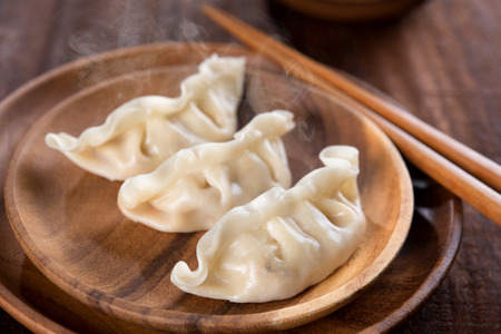 Close up fresh boiled dumplings with hot steams on wood plate. Chinese food on rustic old vintage wooden background. Standard-Bild