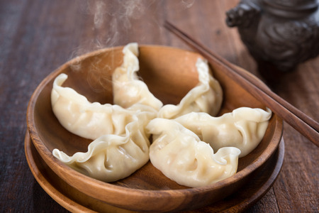 Fresh dumplings with hot steams on wood plate. Famous Chinese cuisine on rustic old vintage wooden background.