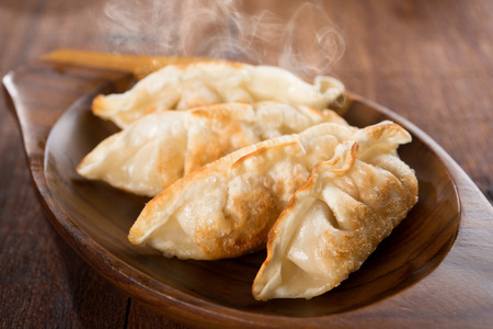 gyoza: Fresh pan fried dumplings on plate with hot steams. Asian meal on rustic old vintage wooden background. Stock Photo