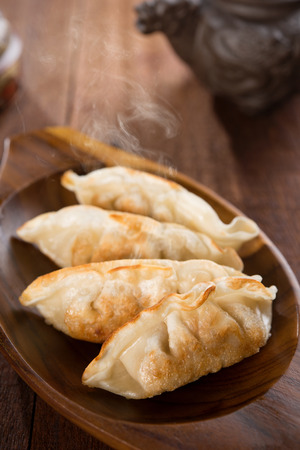 pan asian: Fresh pan fried dumplings on plate with hot steams. Asian food on rustic old vintage wooden background.