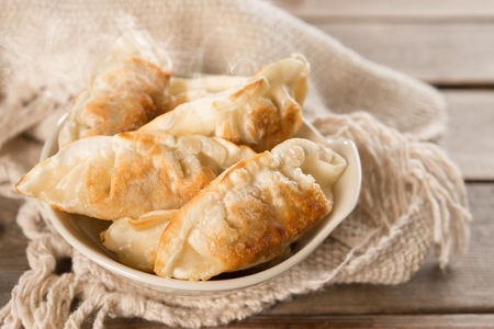 pan asian: Fresh pan fried dumplings on bowl with hot steams. Asian dish on rustic vintage wooden background. Stock Photo