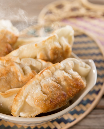 pan asian: Fresh pan fried dumplings on bowl with hot steams. Asian food on rustic vintage wooden background. Stock Photo