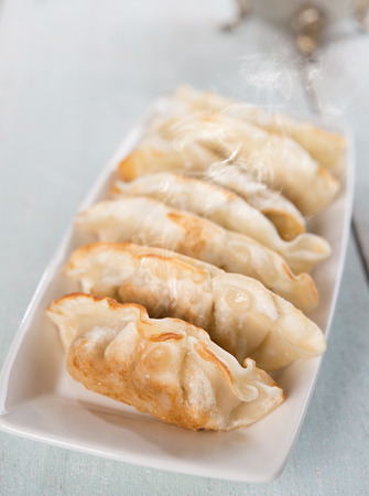 pans: Fresh pan fried dumplings on plate with hot steams. Asian dish on rustic vintage wooden background.