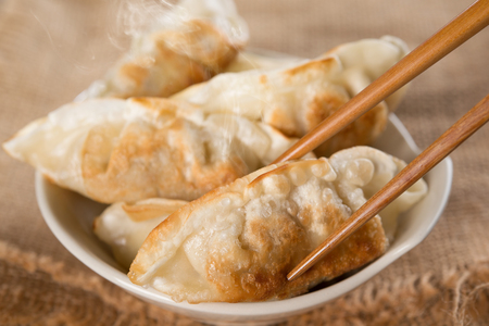 pan asian: Close up fresh pan fried dumplings on bowl with chopsticks and hot steams. Asian food on rustic vintage wooden background.