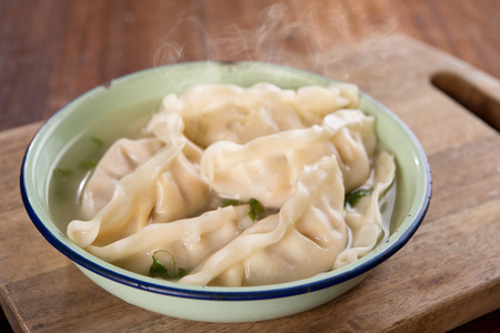 popular soup: Fresh dumplings soup on plate with hot steams. Chinese cuisine on rustic old wooden background.