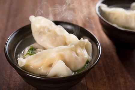 熱い蒸気で板に新鮮な餃子スープ。素朴な古いビンテージ木製の背景に中国のグルメ。