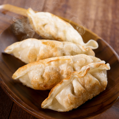 pan asian: Fresh pan fried dumplings on plate with hot steams. Asian dish on rustic old vintage wooden background.