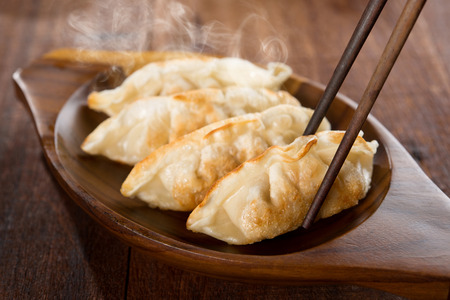 Close up fresh pan fried dumplings on plate with chopsticks and hot steams. Asian food on old rustic vintage wooden background.